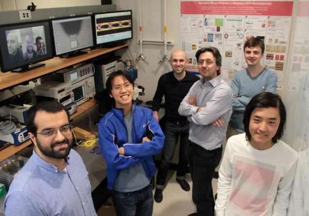 Boston University team in their laboratory joined by co-lead authors (left to right) Amir Atabaki, Fabio Pavanello and Sajjad Moazeni via video conference. Left to right in the photo: Kenaish Al Qubaisi, Imbert Wang, Hayk Gevorgyan, Assistant Professor Milos Popovic (ECE), Anatoly Khilo, and Bohan Zhang.(photo credit: Josep Fargas)
