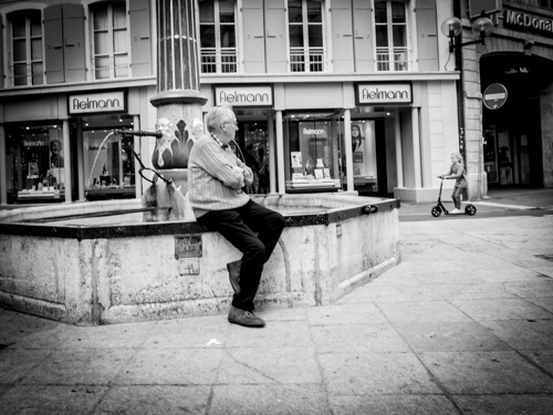 A man waiting for someone, sitting on a fountain in Neuchatel, Switzerland.