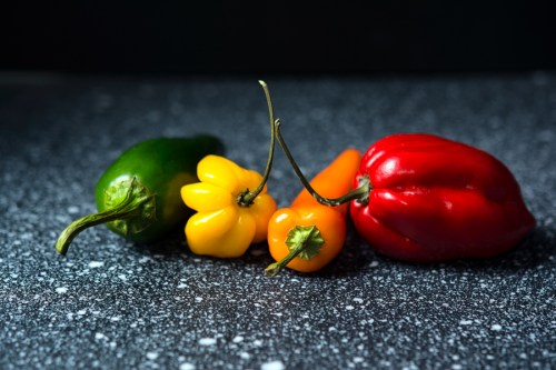 Fresh chili fruits in green, yellow, orange and red.