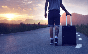 man with luggage on the road