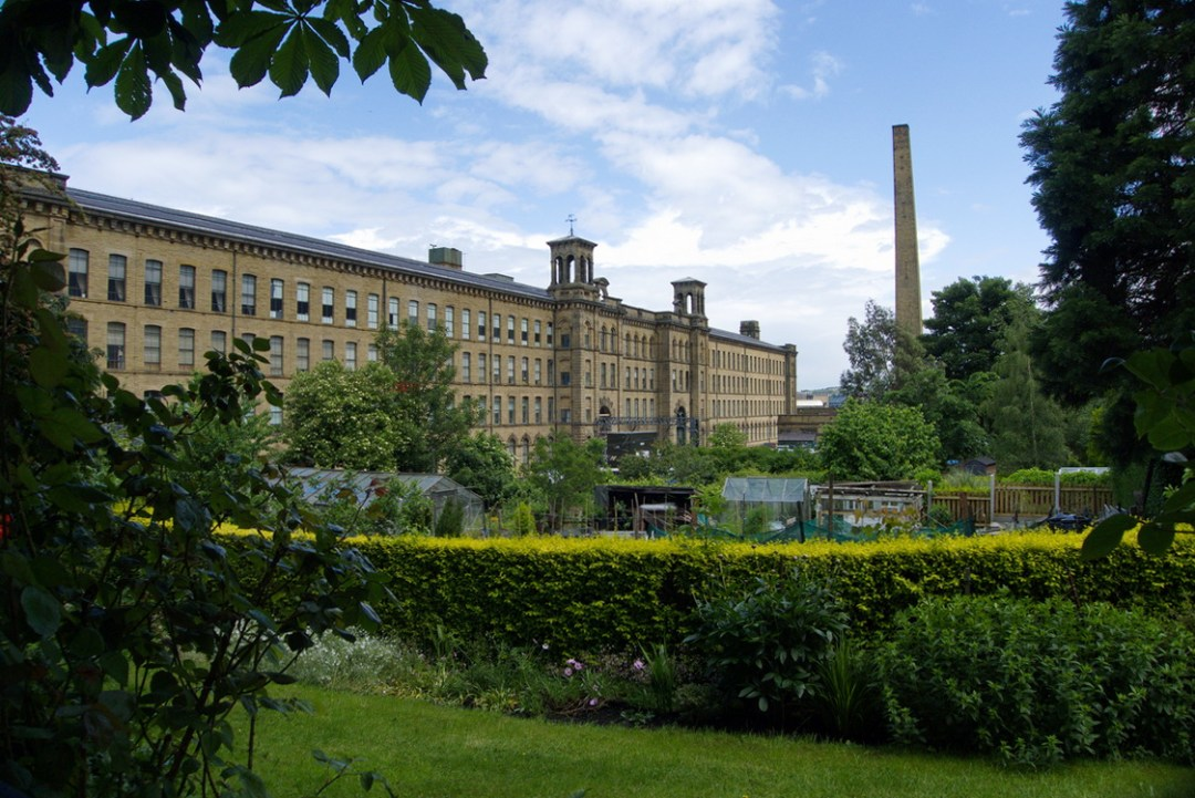 Foreground: shubbery and green grass. Behind: a long, buff-coloured mill building with rows of identical windows all along each of the 4 stories, and a very tall smokestack, against a blue sky