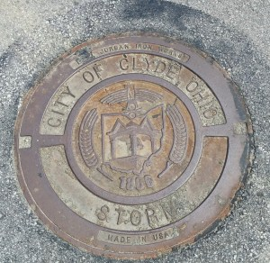 Seal of the city of Clyde on a sewer lid near the Presbyterian church (author's photo).