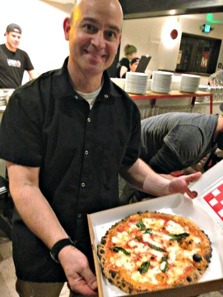 Chris Bryan and pizza; photo L. Goldman