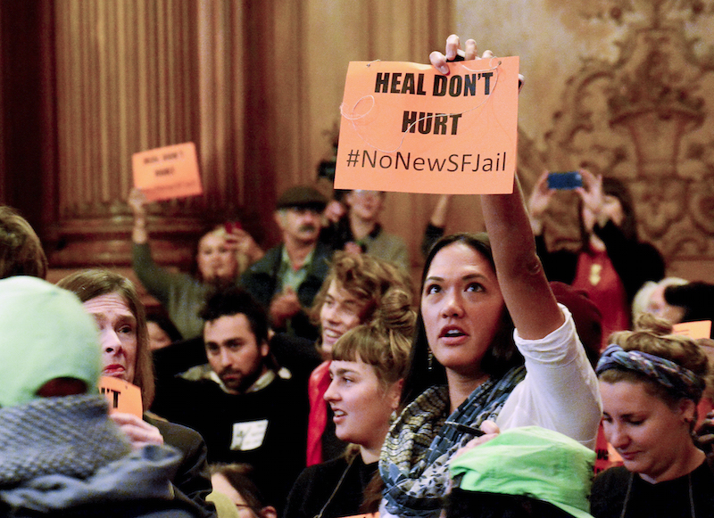 A protester displays a sign opposing the building of a new jail facility in San Francisco, during a budget and finance comittee meeting at San Francisco's city hall Wednesday, December 2, 2015. (Connor Hunt/Special to the S.F. Examiner)