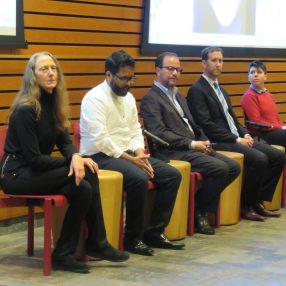 Five of six panelists sit in red chairs before the room, backed by a wood panel wall and large drop-down screens. L to R: (1) Jeanne Hallacy, (2) Dr. Mohammed Zaher Sahloul, (3) Tauseef Akbar, (4) Brad Sugar, (5) Jess Benjamin.