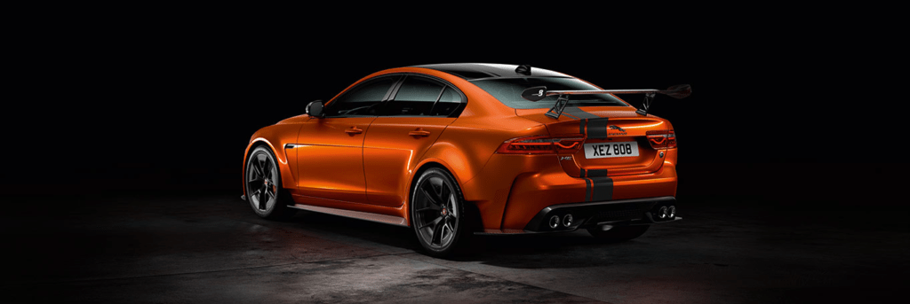 An orange Jaguar XE SV Project 8 from the back with a black background