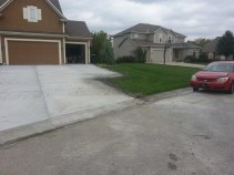 Dirt/seed and mulch reparing next to a new driveway.