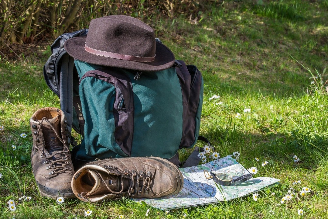 Backpack, hat, trekking shoes, map and compass are part of backpacker's checklist