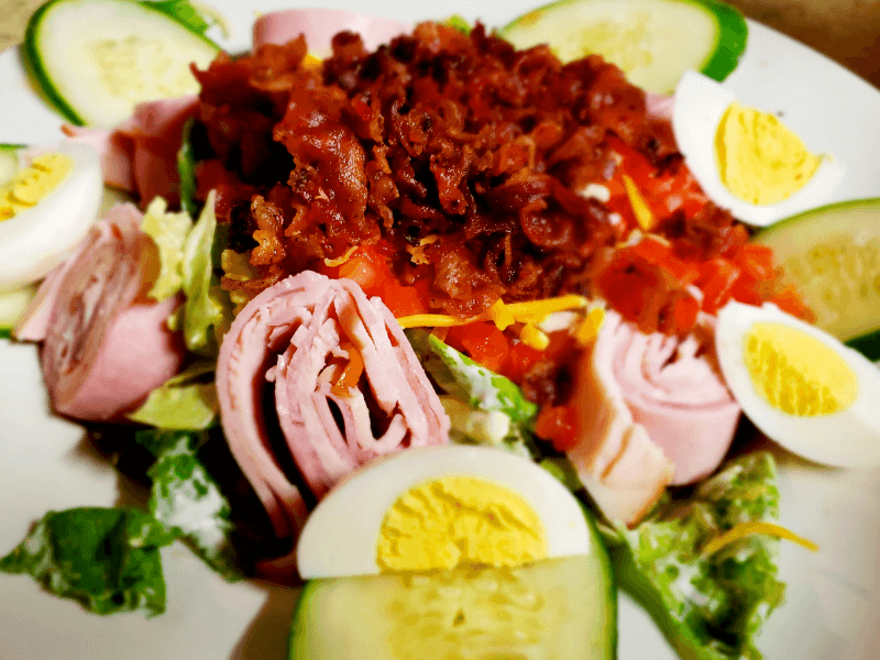Caroline's Salad Deluxe - Turkey, ham, crisp bacon, tomatoes, hard cooked eggs, cucumbers, cheddar and jack cheese, romaine lettuce, and homemade ranch dressing