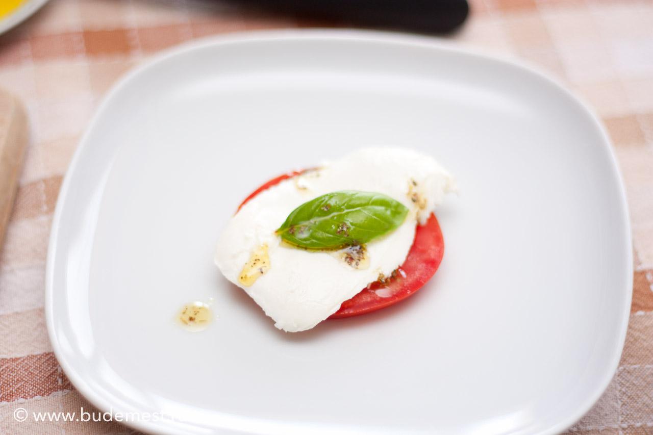 Уложите по кругу на тарелке томат, моцареллу, листок базилика и полейте ароматизированным маслом