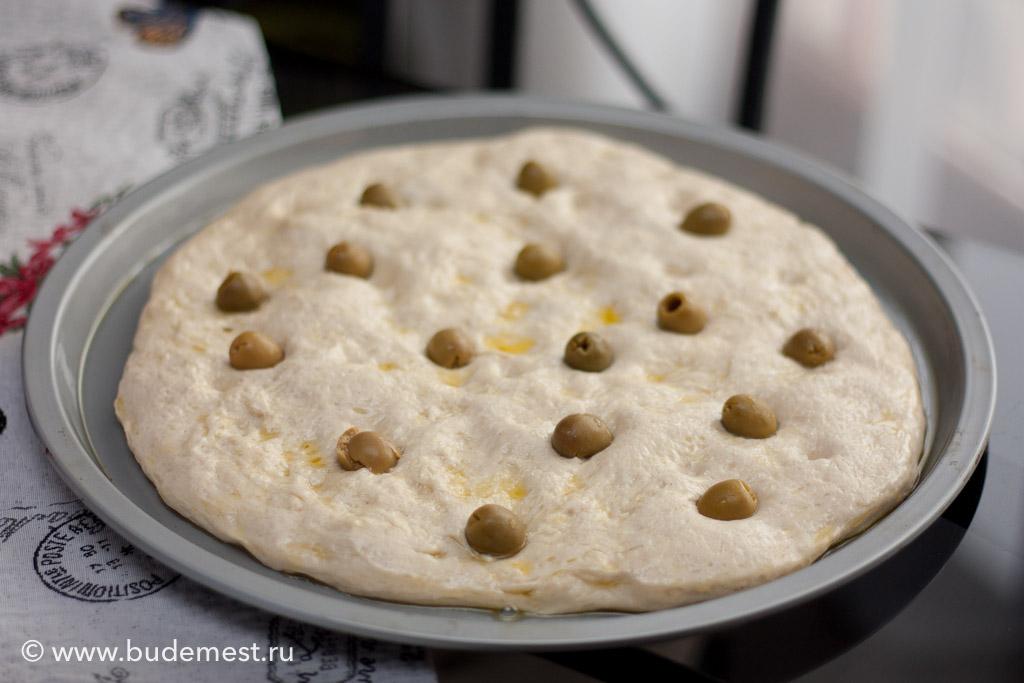 Аккуратно растяните тесто в противне, сделайте канавки пальчиками, посыпьте крупной морской солью, вдавите по канавкам оливки, проткните вилочкой и оставьте отдохнуть на 30 минут