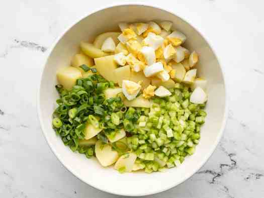 Potatoes, eggs, green onion, and celery in a bowl