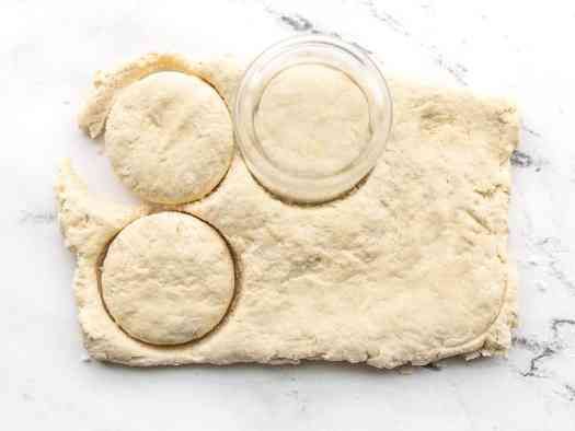 Biscuits being cut out of the dough with a drinking glass