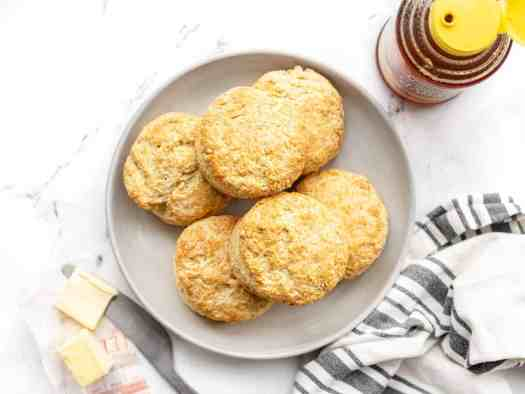 Overhead view of a plate full of butter biscuits with honey and butter on the sides
