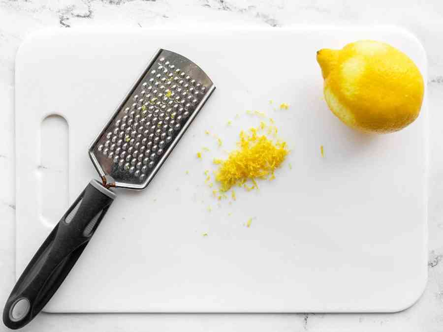 Zested lemon on a cutting board with a small-holed cheese grater