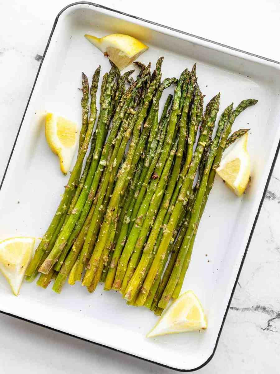 Lemon Garlic Roasted Asparagus on a white roasting pan with lemon wedges
