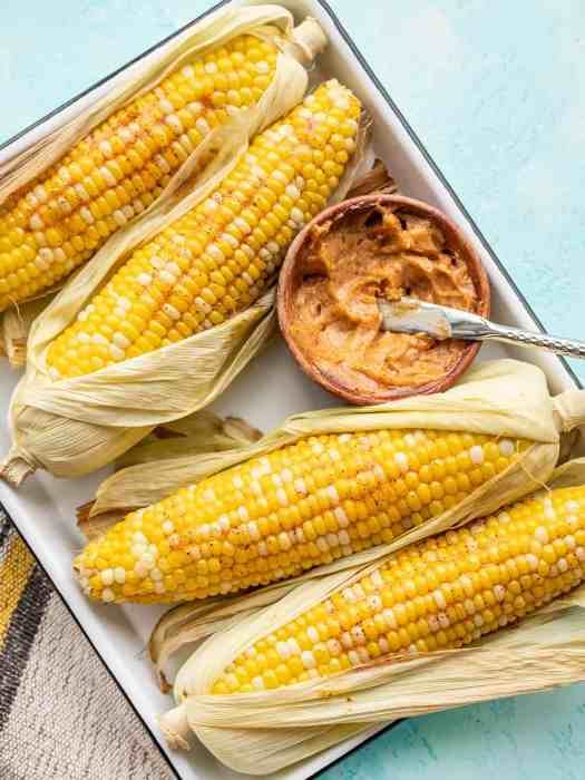 Oven roasted corn half shucked and smeared with honey chili butter on a white tray with a bowl of butter