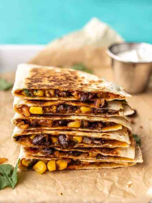 A stack of black bean quesadillas on a tray with a dish of sour cream behind them