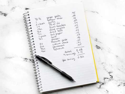 A notebook with a recipe written down and prices listed for each ingredient