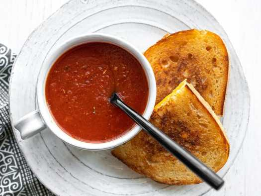 Overhead view of a mug full of tomato soup with a black spoon in the center