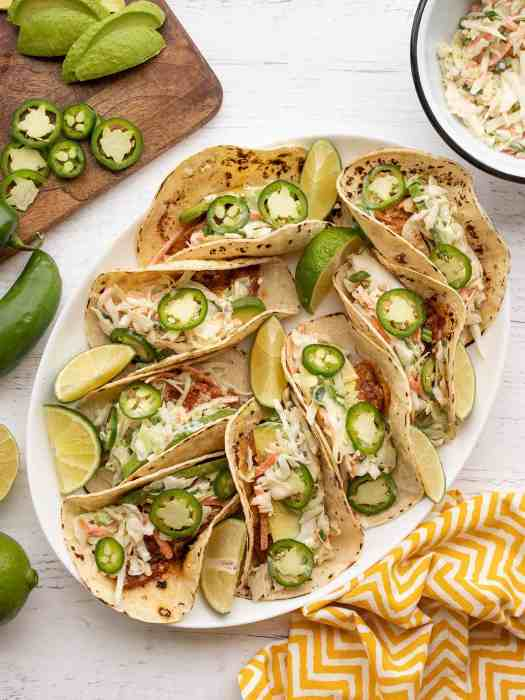 Overhead view of fish tacos on a platter, toppings on the sides