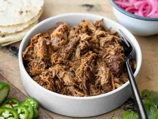 Front view of a bowl full of chili rubbed pulled pork with taco fixings in the back