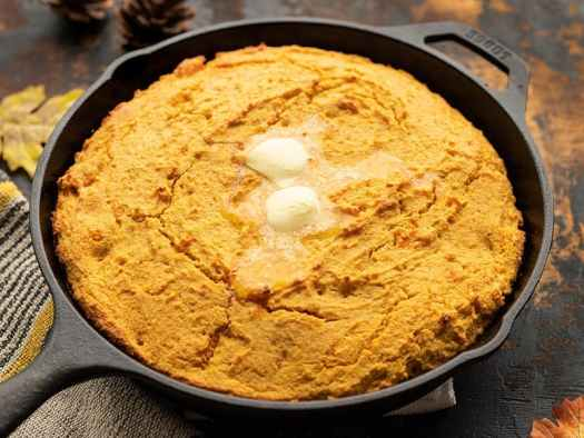 Front view of sweet potato cornbread in the skillet with butter melting on top