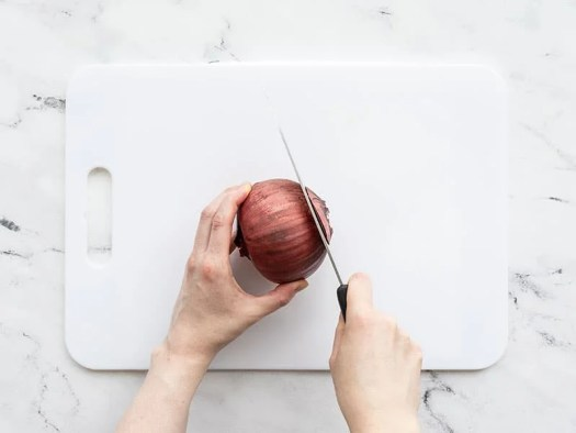 Root end of a red onion being cut off
