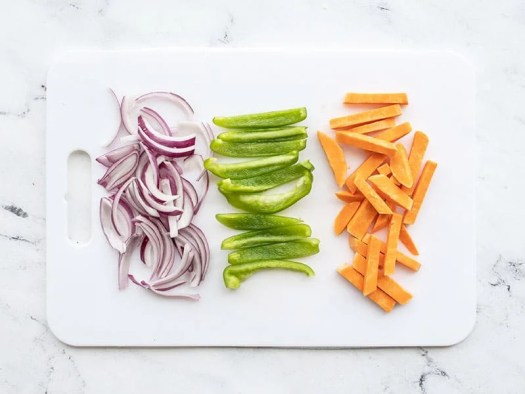 A white cutting board with sliced red onion, bell pepper, and sweet potato