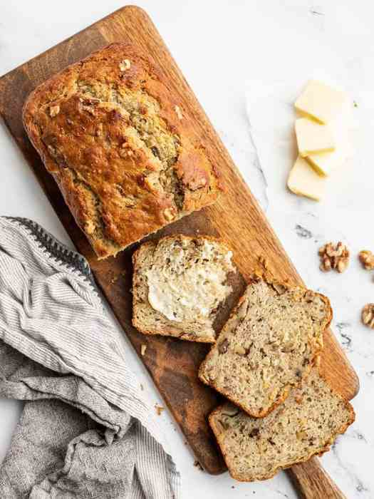 A loaf of banana bread on a narrow wooden cutting board, a few slices cut from the loaf and butter spread on one slice.