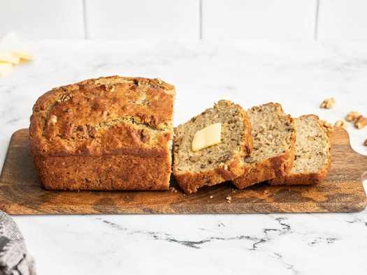 Side view of a loaf of yogurt banana bread on a wooden cutting board, half of it sliced, one slice with butter