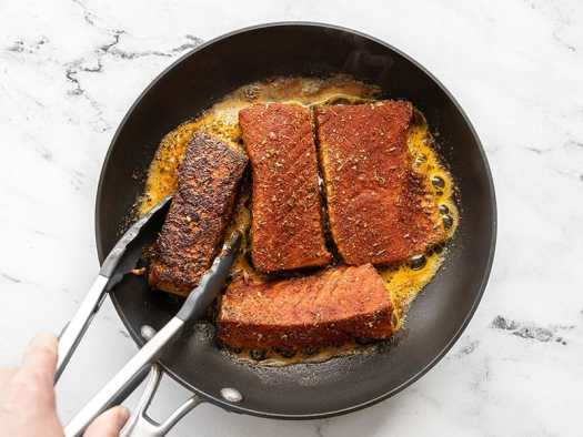 Blackened salmon being turned with tongs in the skillet