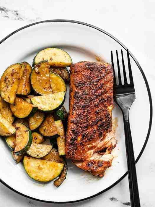 Blackened salmon with zucchini on a white plate with a black fork