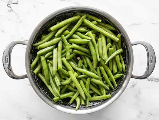 Fresh green beans in the steam basket in the pot, uncooked