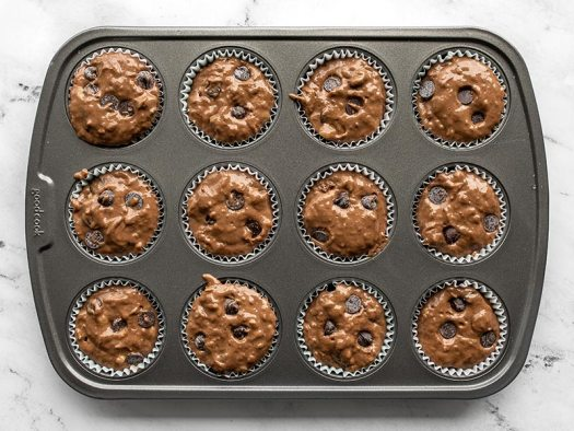 Muffin batter in the muffin tin, unbaked.
