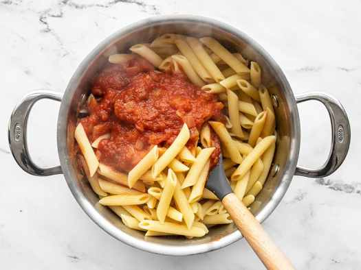 Stirring red sauce into cooked pasta.