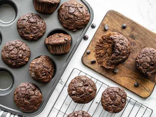 Chocolate banana muffins in the muffin tin, on a cooling rack, and on a cutting board