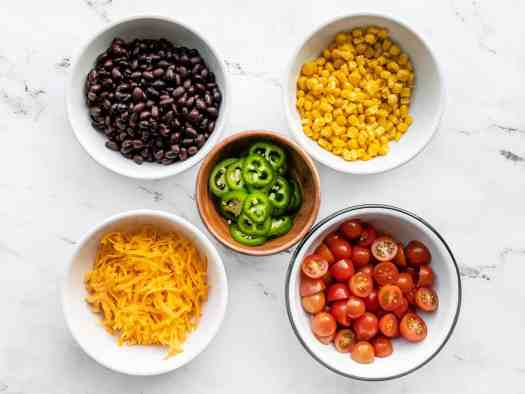 turkey taco salad toppings in bowls: beans, corn, cheese, tomatoes, jalapeño