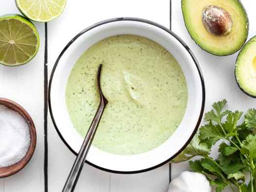 Creamy avocado dressing in a bowl with a black spoon in the center