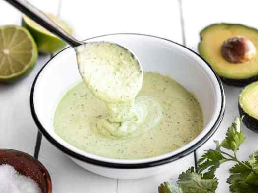 Creamy avocado dressing dripping off a spoon into a bowl