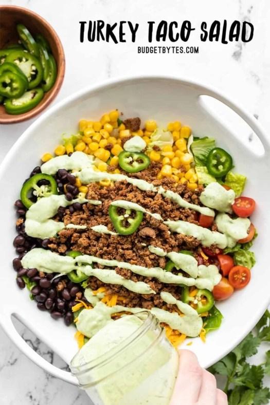 avocado dressing being poured over a turkey taco salad