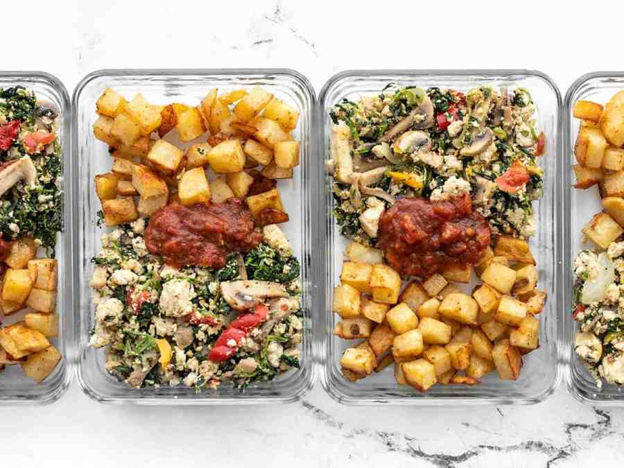 vegetable tofu scramble in glass meal prep containers with roasted potatoes