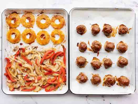 Finished sheet pans with meatballs, peppers, onions, and pineapple