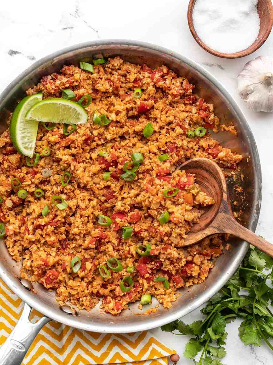 Overhead view of a skillet full of Southwest Cauliflower Rice garnished with lime and a bowl of salt on the side