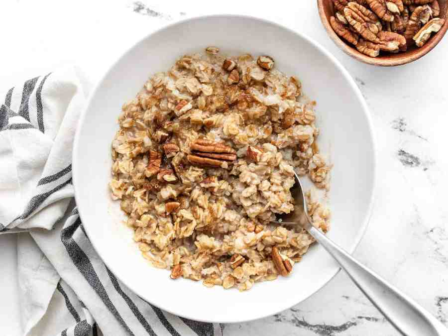 Overhead view of a bowl full of cinnamon pecan cauli oats with a spoon in the center