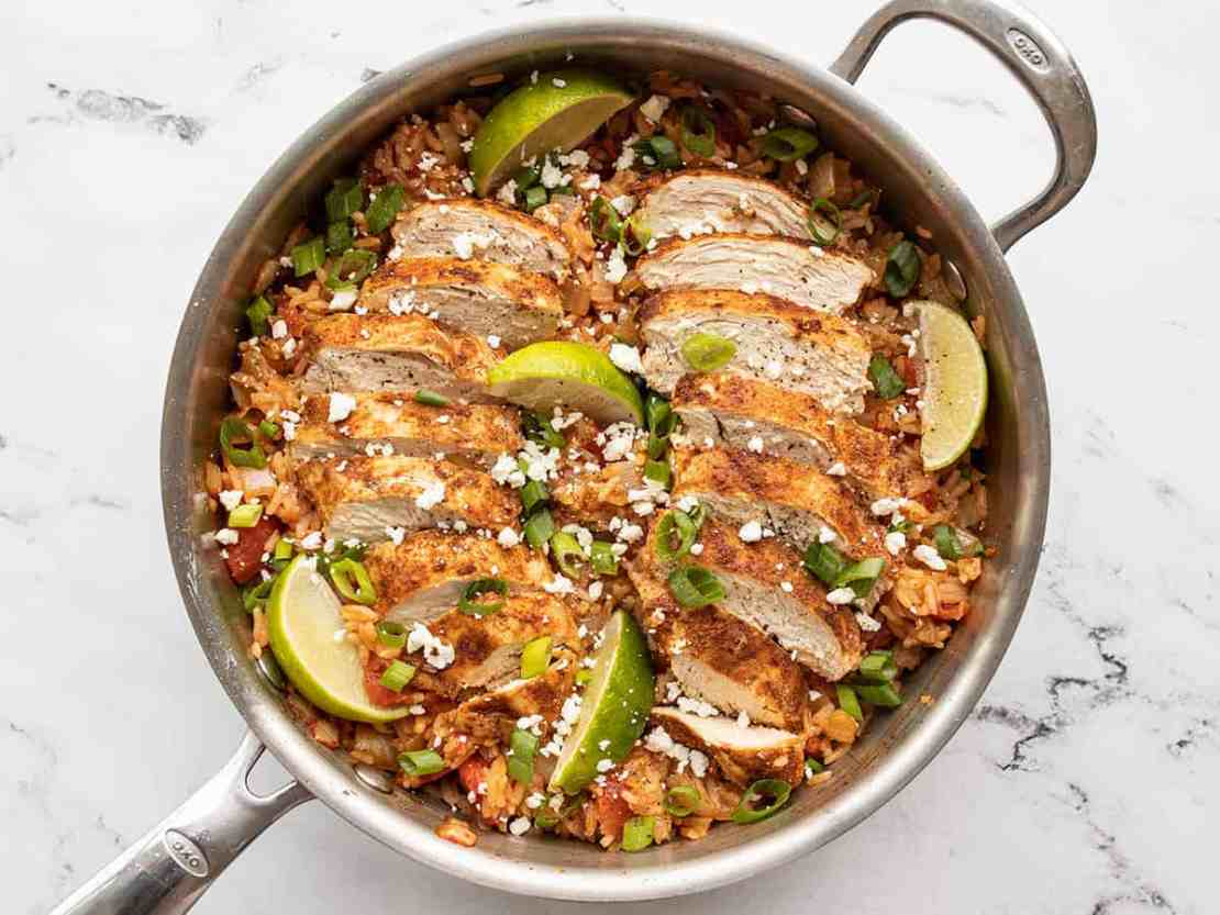 Chipotle lime chicken and rice garnished with cotija, green onion, and limes