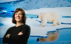 Charlotte Lindqvist in front of a background showing a polar bear walking in a cold climate