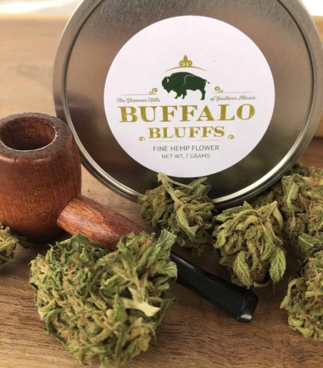 A tin of hemp flower with buds and small wooden pipe