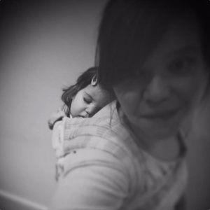 mama met baby op de rug in een draagdoek