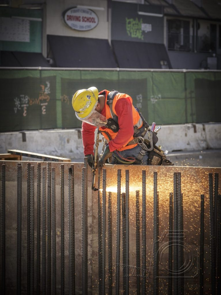Construction workwr uses a welding torch to cut down rebar